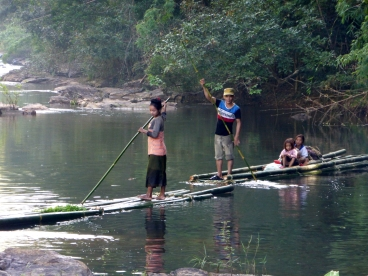 A local family making their way down river on their crop of Bamboo.