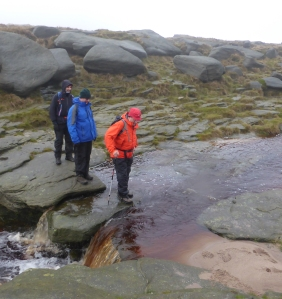 Crossing the River Kinder above the Downfall. Bill in the Hi-Vis jacket is taking it safely.